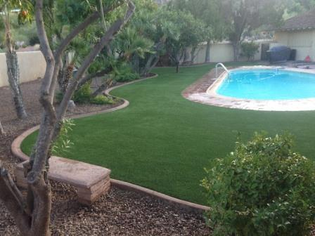 Residential pool surrounded by synthetic grass